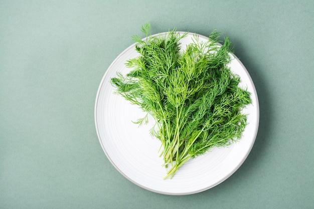 Ein bündel frischer dill auf einem teller auf grünem hintergrund. vitamingrüns in einer gesunden ernährung. ansicht von oben