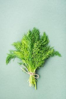 Ein bündel frischer dill mit einem seil auf grünem hintergrund gebunden. vitamingrüns in einer gesunden ernährung. ansicht von oben und vertikal
