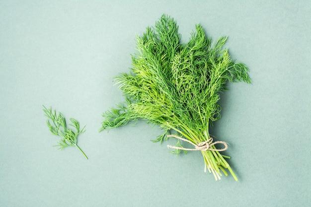 Ein bündel frischer dill mit einem seil auf grünem hintergrund gebunden. vitamingrüns in einer gesunden ernährung. ansicht von oben