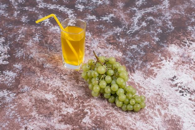 Ein bündel grüner trauben und ein glas saft