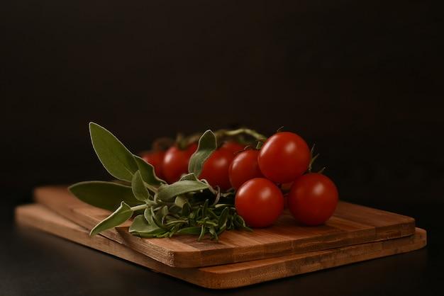 Ein bündel grüns zum kochen von fleisch, bestehend aus rosmarin und salbei, liegt auf einem hölzernen schneidebrett.