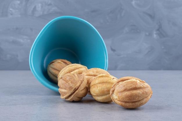 Ein bündel mit karamell gefüllte kekskugeln, die aus einer kleinen schüssel auf marmor verschüttet wurden