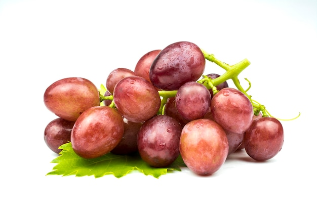Ein bündel reife rosa trauben liegt auf einem grünen blatt, das auf einem weißen hintergrund lokalisiert wird.
