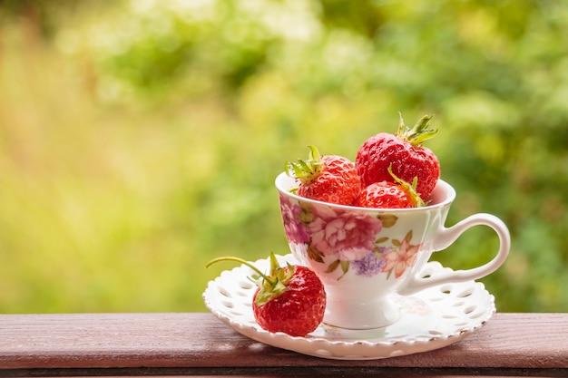 Ein bündel reifer saft erdbeeren in einer tasse auf holztisch. frische erdbeeren auf dem bauernmarkt. gesundes essen zum frühstück und snack. kopierfläche