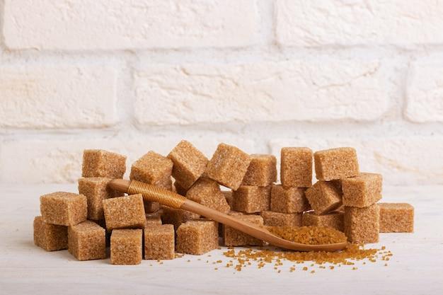 Ein bündel rohrzucker und zuckersand in einem holzlöffel