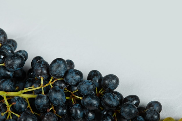 Ein bündel roter trauben auf blauem raum.