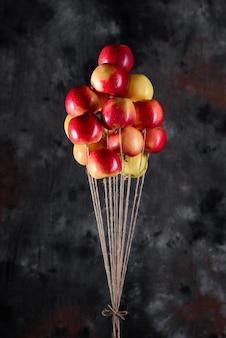 Ein bündel roter und gelber äpfel an einem handgefertigten juteseil, die wie luftballons fliegen. eine erinnerung aus der kindheit. konzeptionelle idee