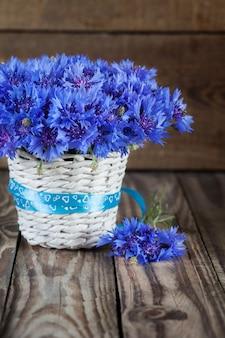 Ein bündel schöne sommerblume von cornflower im weißen eimer mit blauem band.