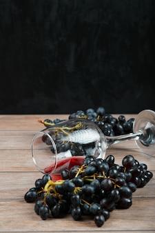 Ein bündel schwarzer trauben und ein glas wein auf dunkler oberfläche