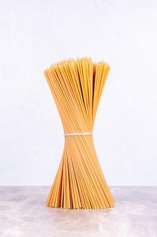 Ein bündel spaghetti isoliert auf dem marmorraum.