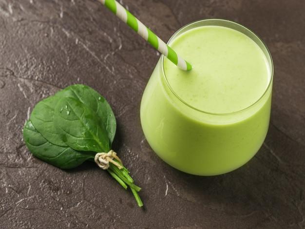 Ein bündel spinatblätter und ein glasglas mit einem smoothie auf steinhintergrund. fitnessprodukt. diätetische sporternährung.