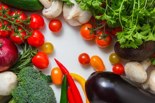 Ein bündel tomaten mit chilischoten, brokkoli, knoblauch, pilzen, auberginen, zwiebel draufsicht auf einer weißen oberfläche