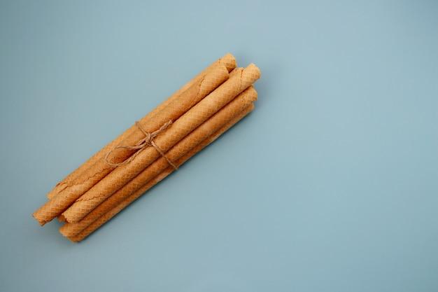 Ein bündel waffelröllchen auf blauem hintergrund lange waffelröllchen