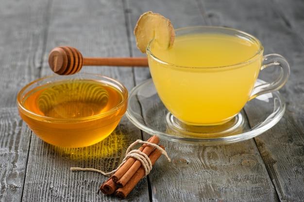 Ein bündel zimtstangen, ingwerwurzel und ein getränk aus ingwer und zitrusfrüchten auf einem tisch.