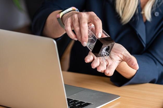 Ein büroangestellter schüttet eine büroklammer aus einem behälter in seine hand, nahaufnahme