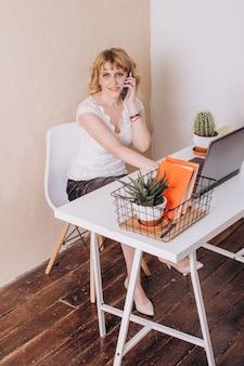 Ein büroangestellter sitzt an einem laptop und telefoniert