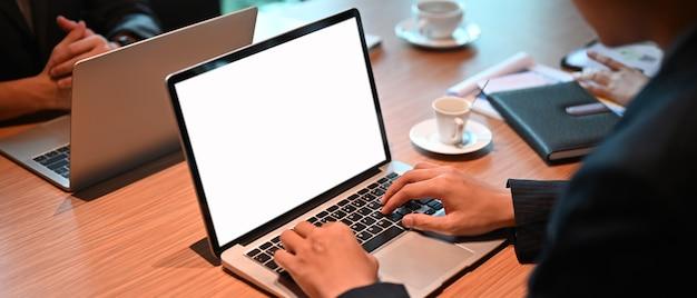 Ein büromann benutzt einen computer-laptop mit einem weißen leeren bildschirm am hölzernen schreibtisch.