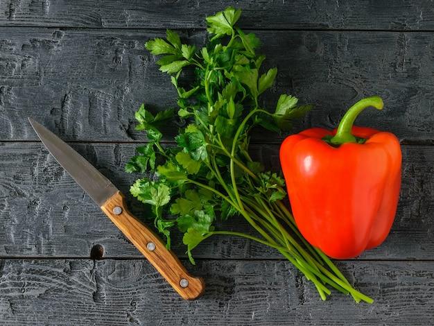 Ein bund petersilie, rote paprika und ein messer auf einem rustikalen holztisch