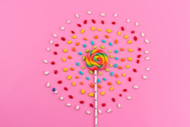Ein bunter lutscher der draufsicht mit farbigen bonbons auf rosa, bonbonfarbenem zuckerregenbogen