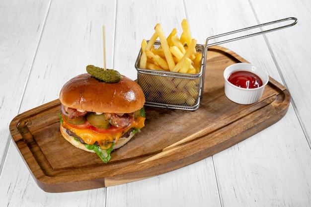 Ein burger und ein korb mit pommes frites mit ketchup auf einem holzschreibtisch