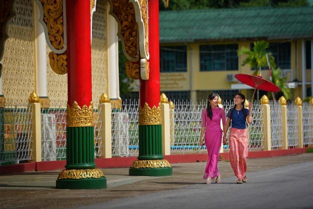 Ein burmesisches mädchen in nationaltracht, verschwommenem hintergrund, wandern und besuch von sehenswürdigkeiten in der shwedagon-pagode in yangon, burma.