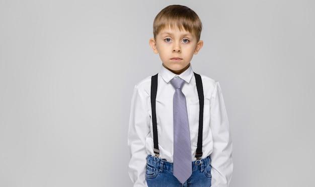 Ein charmanter junge in einem weißen hemd, hosenträgern, einer krawatte und leichten jeans steht auf einem grauen