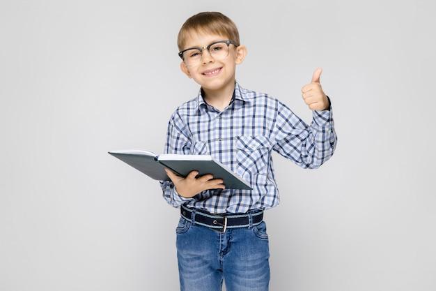 Ein charmanter junge mit einem eingelegten hemd und leichten jeans steht. der junge hält ein buch in den händen. junge mit brille