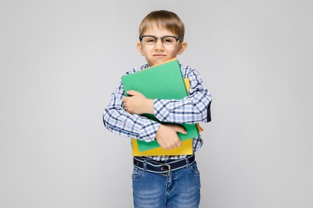 Ein charmanter junge mit einem vkletchatoy-hemd und einer hellen jeans steht auf einem grau. der junge hält in seinen händen eine bunte mappe mit dokumenten