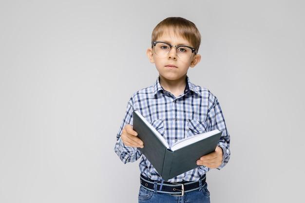 Ein charmanter junge mit eingelegtem hemd und leichter jeans steht auf grau