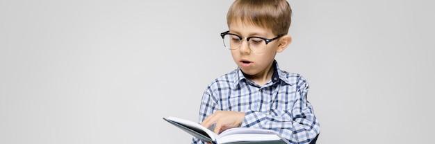 Ein charmanter junge mit eingelegtem hemd und leichter jeans steht. der junge hält ein buch in den händen. junge mit brille