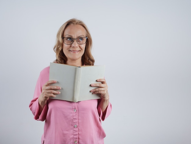 Ein charmanter lehrer mit einem aufgeschlagenen buch in der hand, der eine brille trägt und nach einem porträt schaut