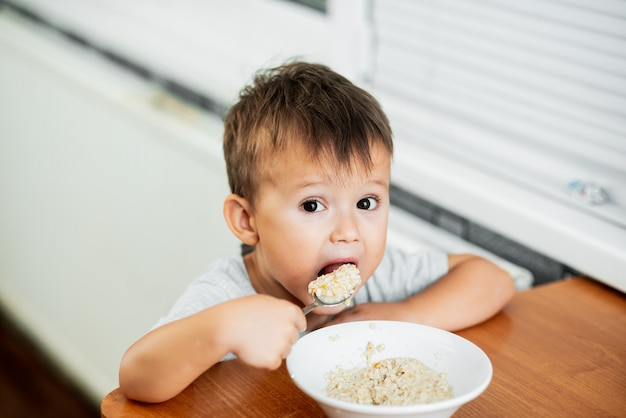 Ein charmantes kind in einem t-shirt in der küche isst sehr gierig haferflocken