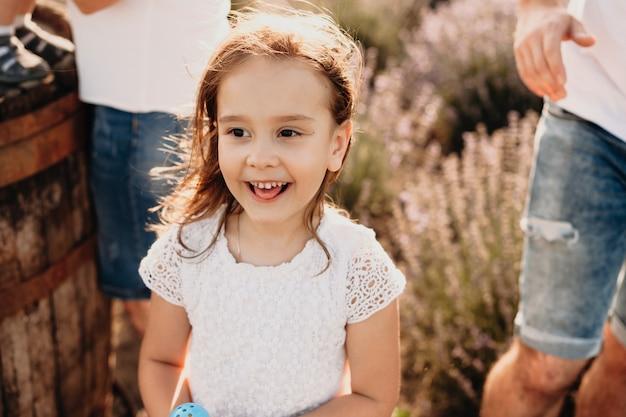 Ein charmantes kleines mädchen, das auf einem lavendelfeld posiert, lächelt glücklich und hat freude, umgeben von vielen emotionen