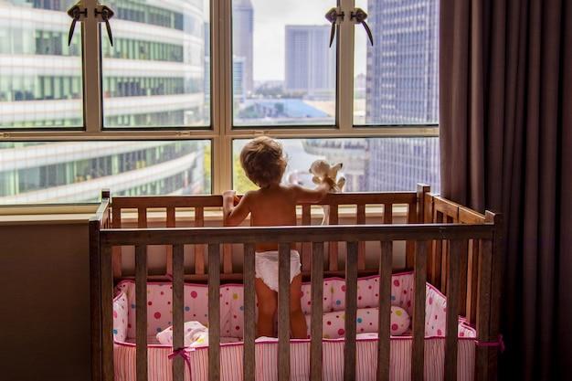 Ein charmantes kleinkind schaut aus dem fenster auf die metropole, während es in einer krippe steht. baby in einer krippe schaut aus dem fenster auf die stadt. rückansicht weichzeichner