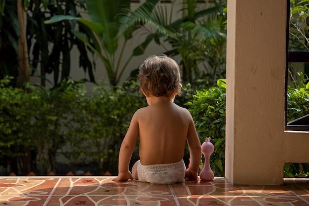Ein charmantes kleinkind sitzt mit einem spielzeug auf den stufen eines hauses im sonnenlicht. rückansicht.