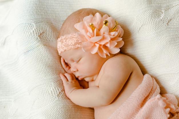 Ein charmantes neugeborenes, eingewickelt in eine zarte rosa decke, schläft auf einem gestrickten plaid. nahaufnahmeportrait.