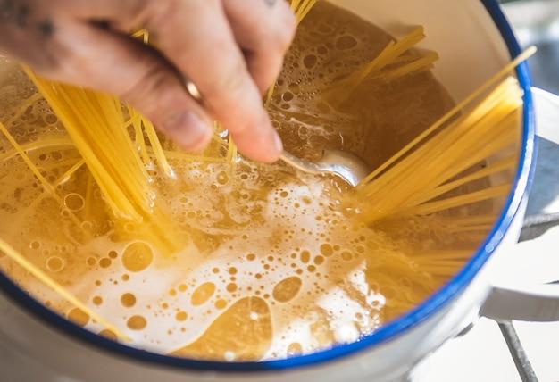 Ein chef, der capellini teigwaren im topf kocht