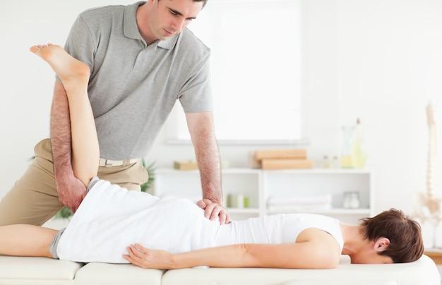 Ein chiropraktiker streckt das bein eines kunden