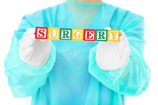 Ein chirurg, der holzklötze mit operationstext hält