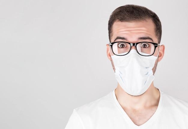 Ein chirurg in einer weißen medizinischen maske und einer brille steht mit überraschung auf einem weißen hintergrund. nach der ansteckung mit covid 19 grippe und saisonale erkältungen.