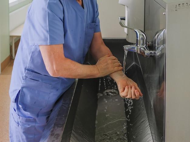Ein chirurg wäscht seine hände unter einem wasserhahn in einem waschbecken aus edelstahl und bereitet sich auf einen chirurgischen eingriff vor.