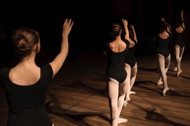 Ein choreografierter tanz einer gruppe anmutiger hübscher junger ballerinas, die auf der bühne einer klassischen ballettschule üben