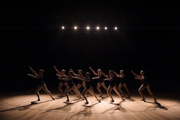 Ein choreografierter tanz einer gruppe anmutiger hübscher junger ballerinas, die in einer klassischen ballettschule auf der bühne üben.
