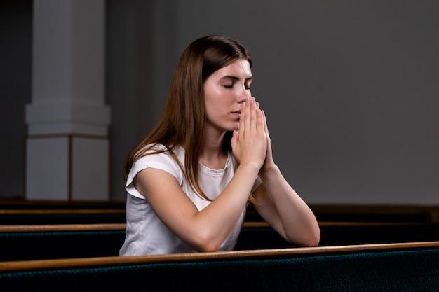 Ein christliches mädchen im weißen hemd sitzt und betet mit demütigem herzen in der kirche