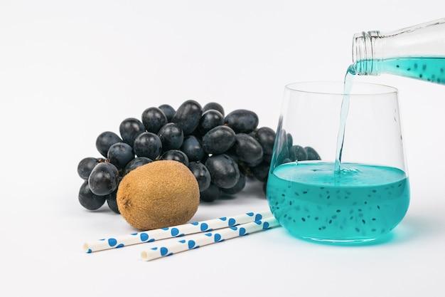 Ein cocktail mit basilikumsamen wird aus einer flasche in ein glas gegen eine oberfläche von trauben gegossen