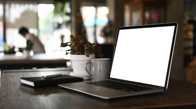 Ein computer-laptop mit leerem bildschirm, eine kaffeetasse und eine notizbuch-werbeanlage stellen einen schwarzen tisch mit einem verschwommenen modernen büroraum auf.