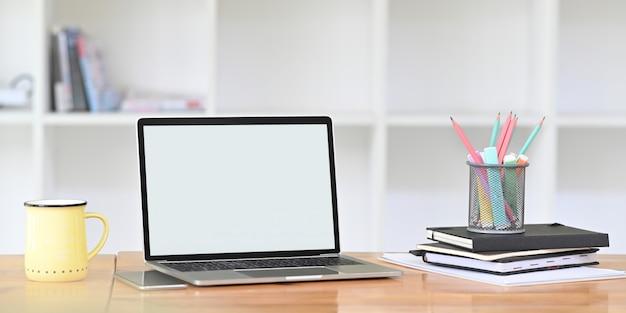 Ein computer-laptop mit leerem bildschirm stellt einen hölzernen schreibtisch auf, der von bürogeräten umgeben ist.