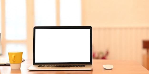 Ein computer-laptop mit leerem bildschirm stellt einen hölzernen schreibtisch auf, der von einer kaffeetasse, einer zwischenablage und einer drahtlosen maus umgeben ist.