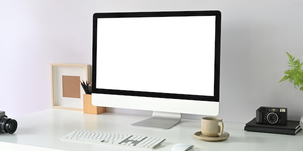 Ein computermonitor mit leerem bildschirm stellt einen weißen schreibtisch auf, der von bürogeräten umgeben ist.