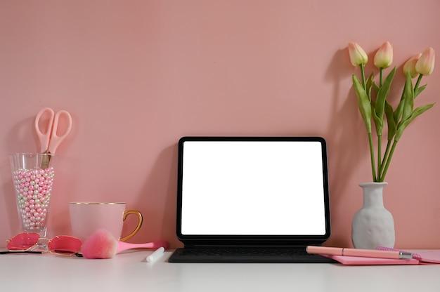 Ein computertablett mit einem weißen leeren bildschirm stellt einen schreibtisch auf, der von verschiedenen geräten umgeben ist.